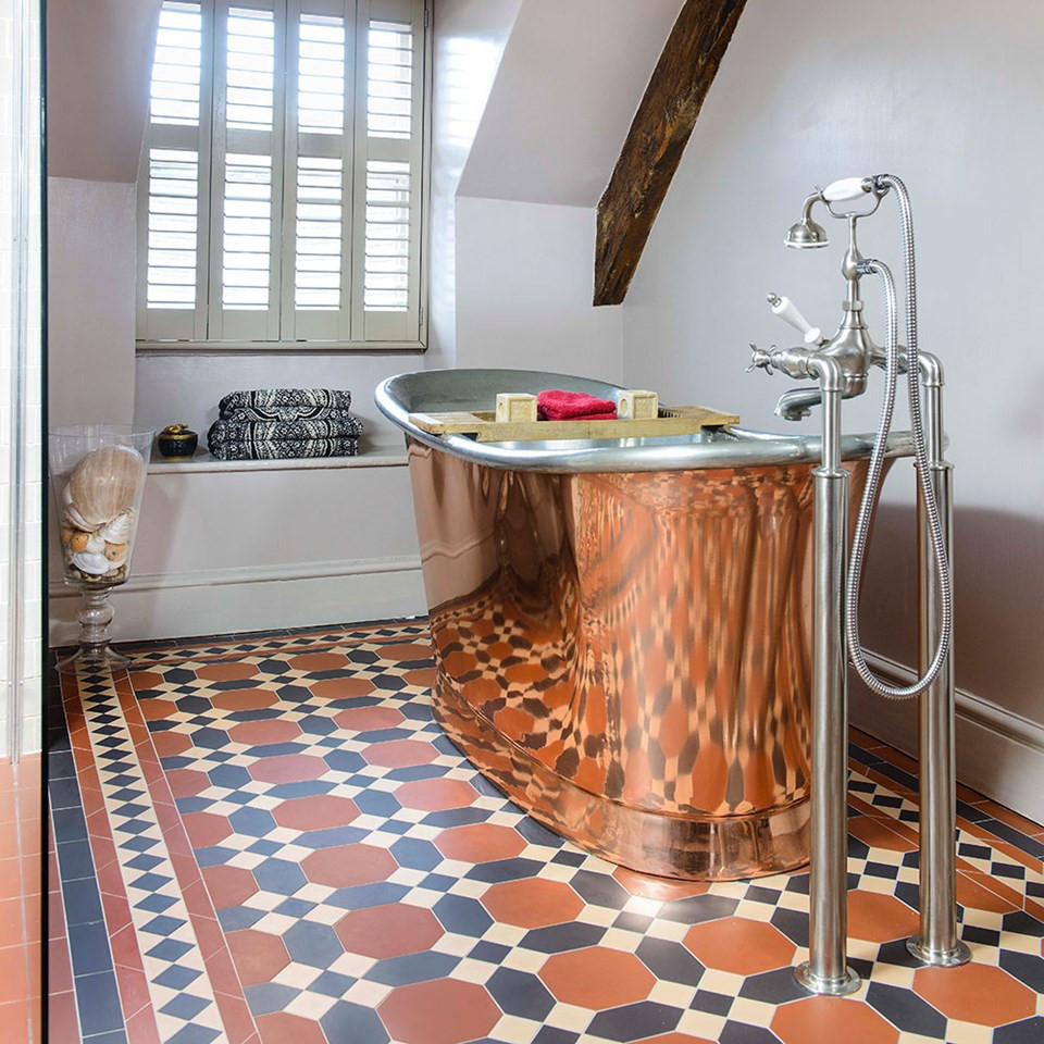 Bathroom with victorian Tiles in terracotta colours and copper bathtub