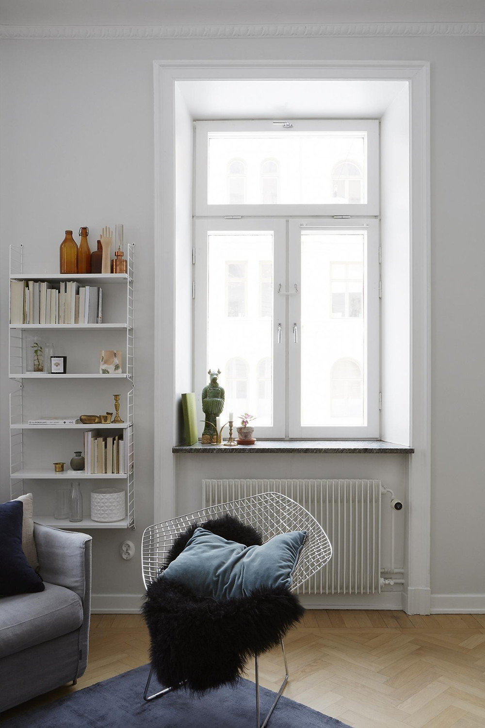 Scandinavian interior design living room with grey sofa and lots of cushions, indigo blue and white walls String shelving unit and apothecary bottles