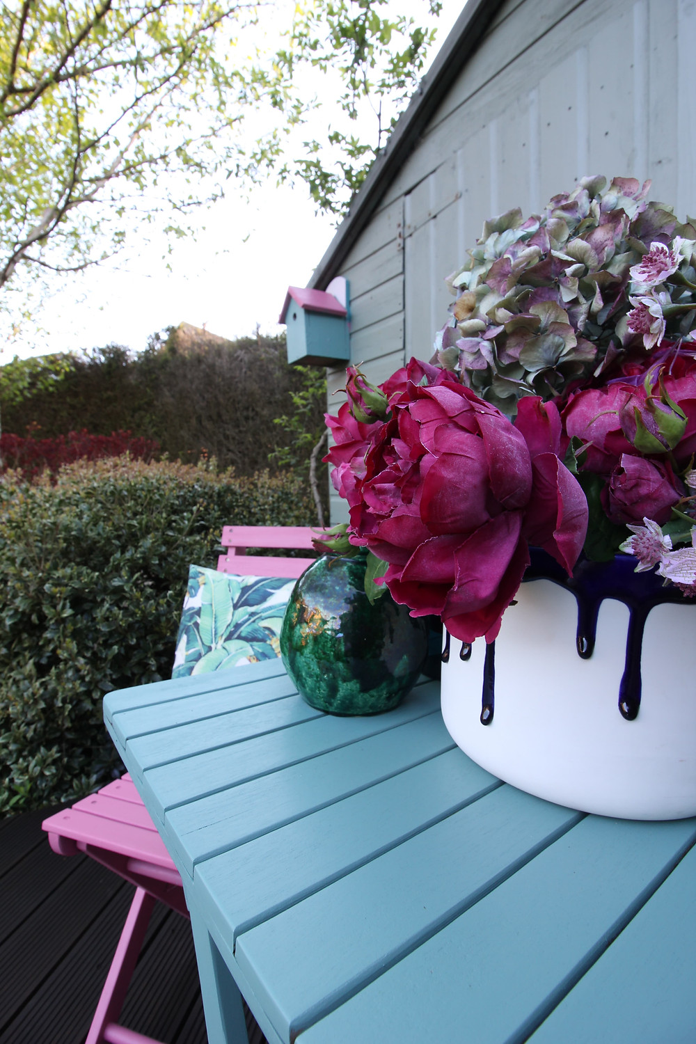 A shed painted slate by Ronseal. A bistrot set with pink and green wooden furniture and flowers in a vase