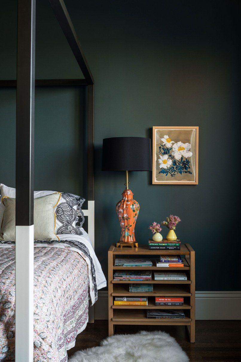 A dark bedroom painted in lead grey or green with four poster bed and white skirting board, art on the wall