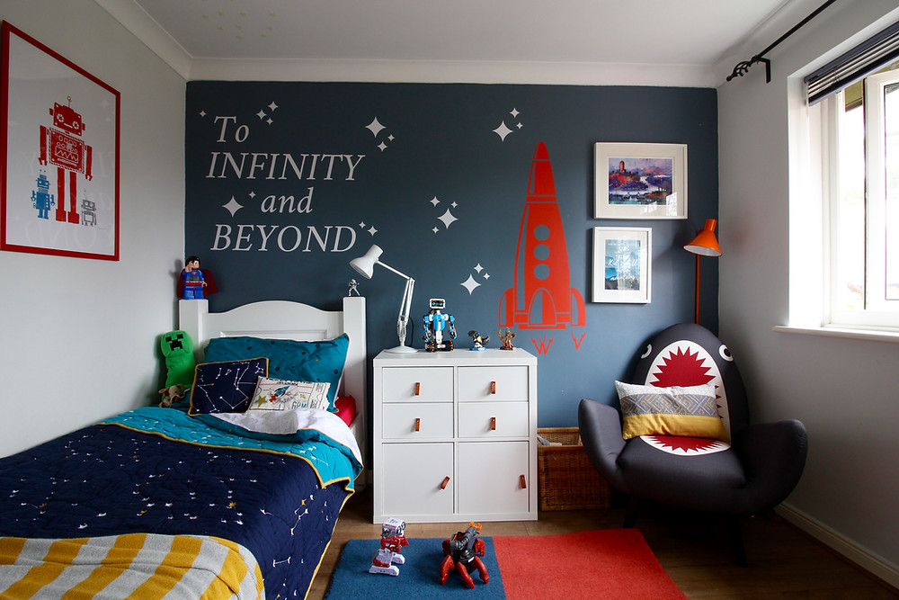 Room Reveal: Spare room turned home office | seasonsincolour.com | a room with blue wall Dulux steel symphony 1 and shark chair by made.com, wall stickers with rocket and ikea kallax storage, a white bed with duvet covered in stars