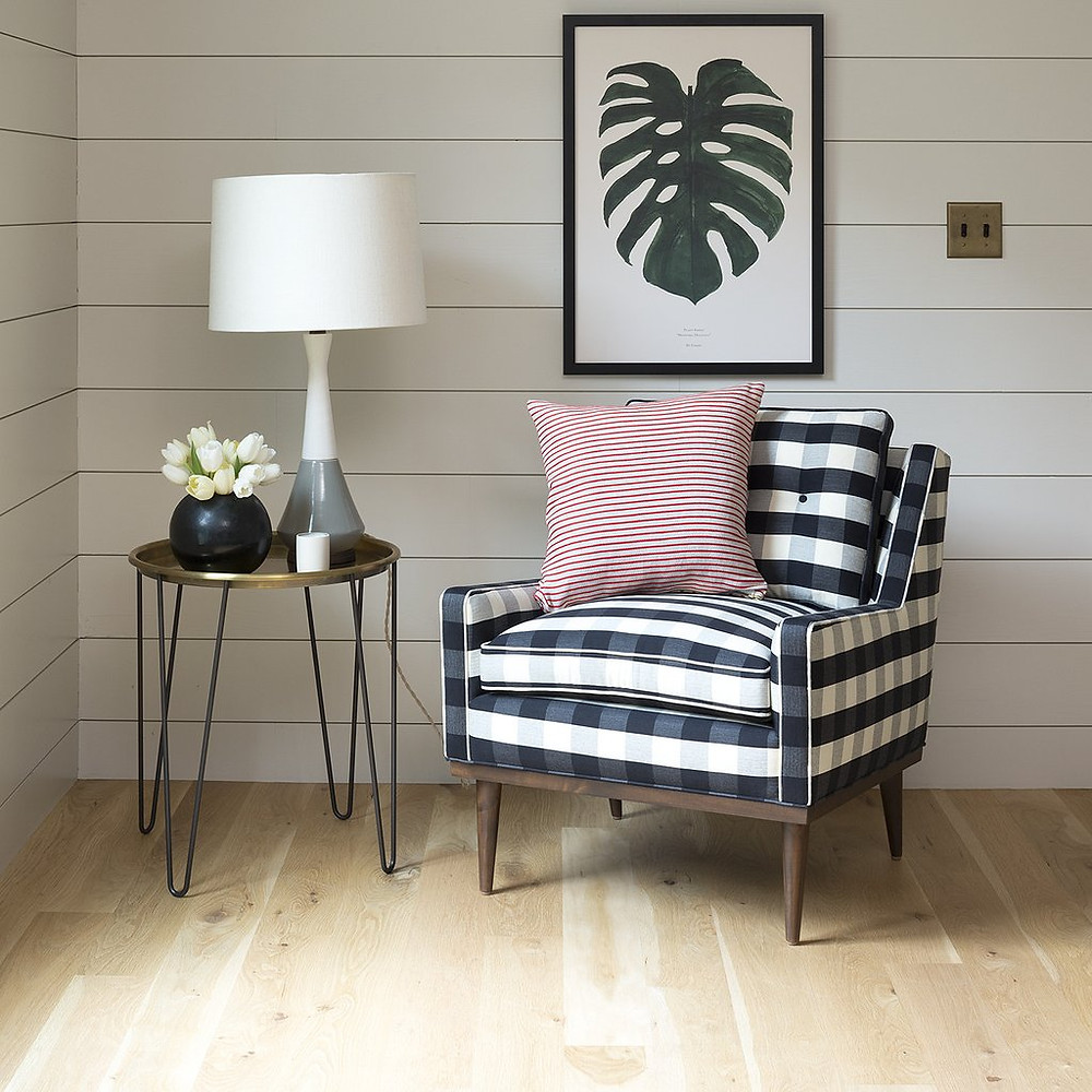 midcentury armchair with plaid fabric in black and white blue metal and brass table and monstrera print