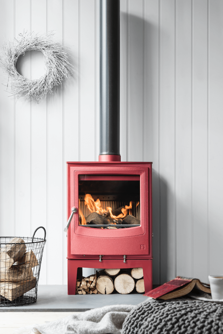 Arada Farringdon wood burning stove in red pink colour in front of a white wall