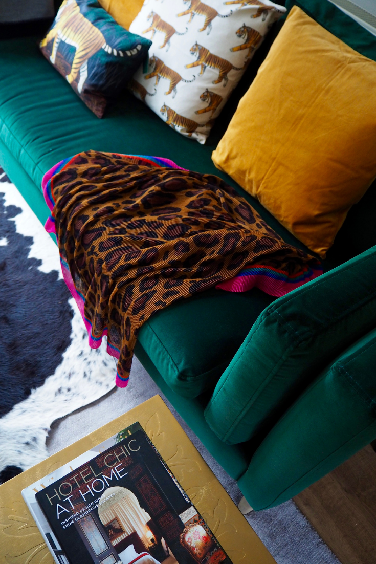 Green velvet sofa with velvet and linen cushions in ochre and in tiger motif from H&M
