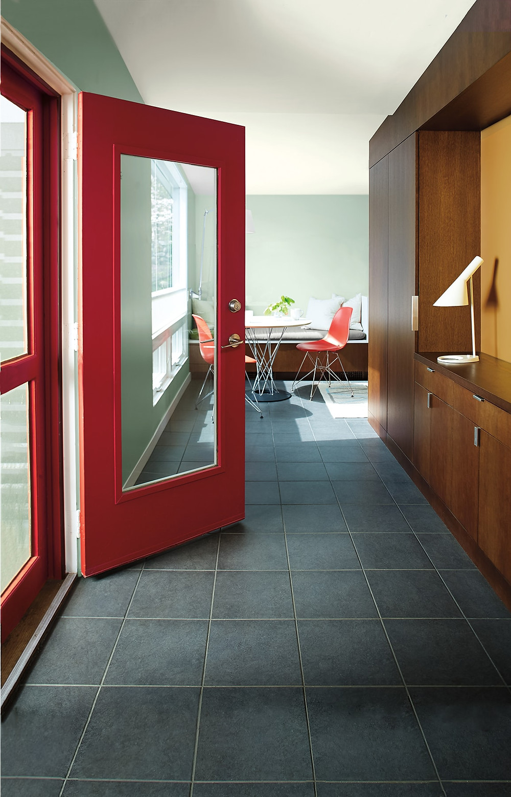 Red door leading to open plan kitchen dining area with mid century vibes, slated floor and red EAMES chairs, mint green wall. Benjamin Moore has revealed Caliente AF-290 as its highly anticipated Colour of the Year 2018. Unveiled alongside a corresponding palette consisting of 22 enlivening hues, this vibrant and charismatic shade of red is a bold yet soothing contemporary colour that oozes confidence. Wall colour - Caliente AF-290, Trim & Door colour - White Opulence OC-69