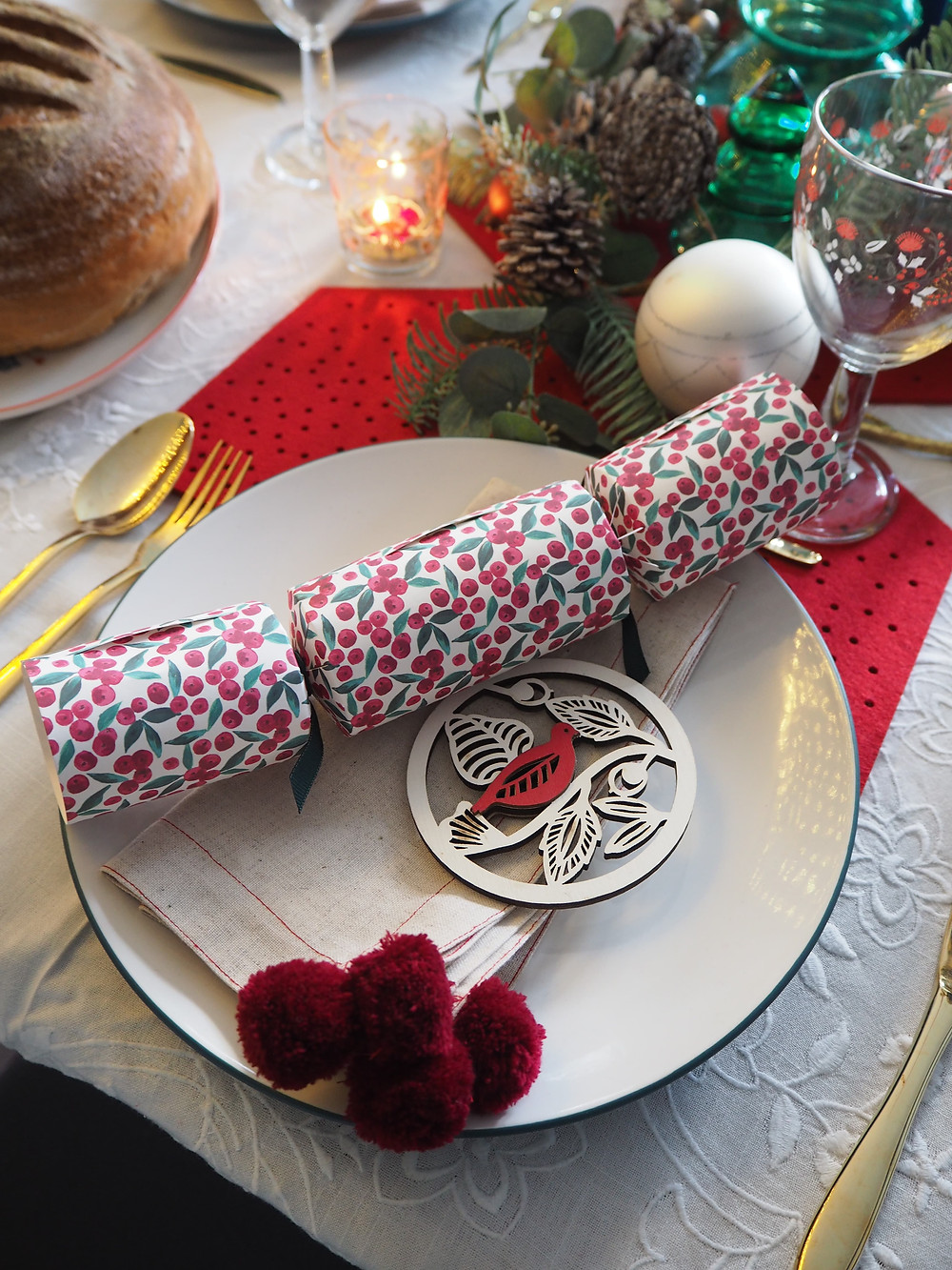 How to set your Christmas table with John Lewis Christmas crackers in pink and green with blue background and fairy lights, felt cracker centrepiece from the Folklore collection. Gold cutlery table setting.