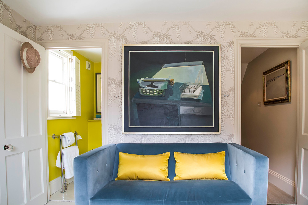 guest bedroom decor ideas with wallpaper, large size art and blue sofa with yellow cushions, yellow bathroom Sarah Vanrenen