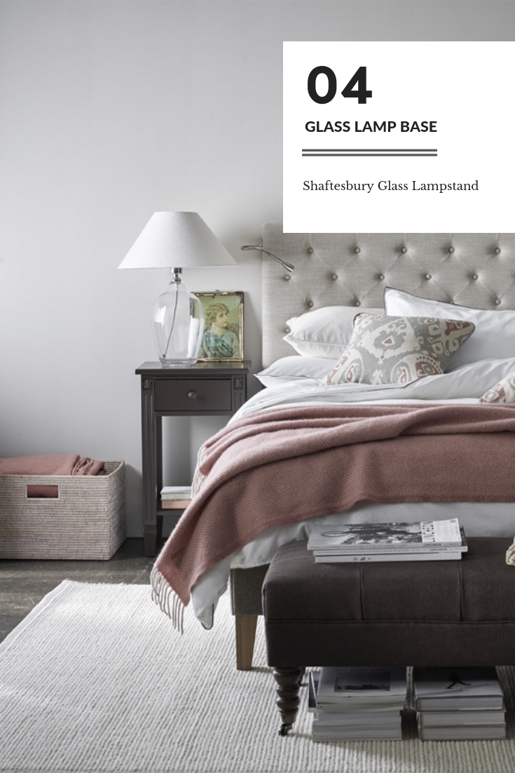 Shaftesbury Glass Lampstand by Neptune on a small bedside table and next to a linen headboard bed with pink throw and a muted colour palette