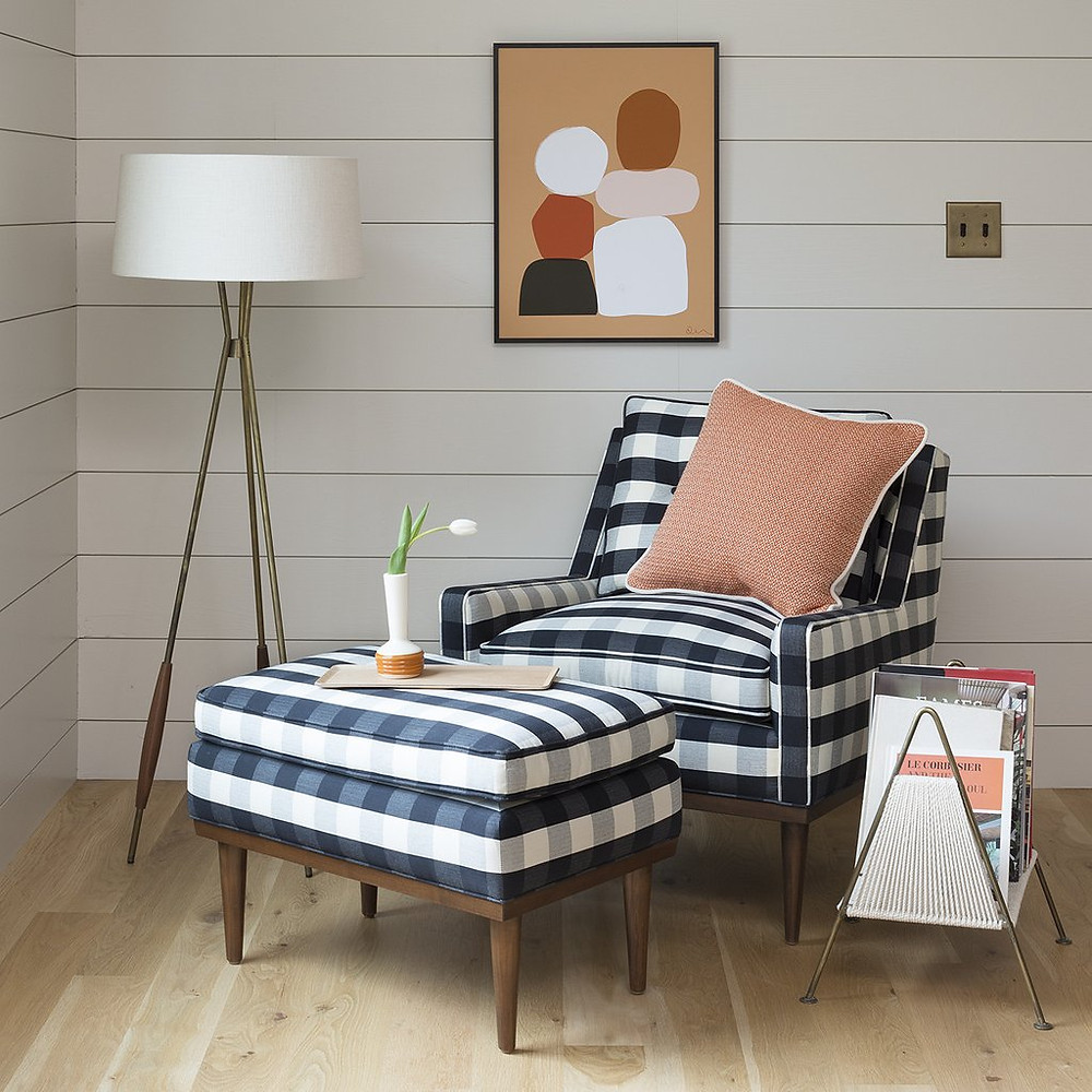 midcentury armchair with plaid fabric in black and white, abstract art and tripod light