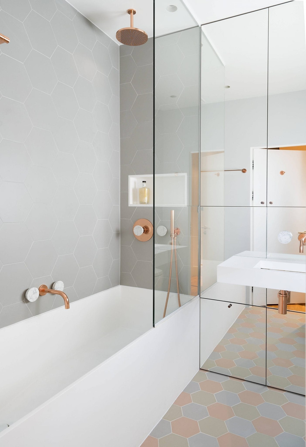 feminine bathroom with mirrors and rose gold taps pastel colour tiles