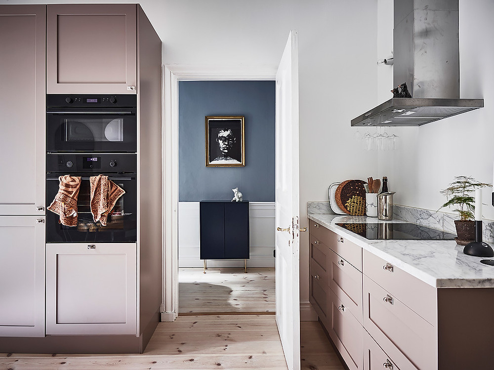 kitchen in pink cupboards and blue hallway with black and white art