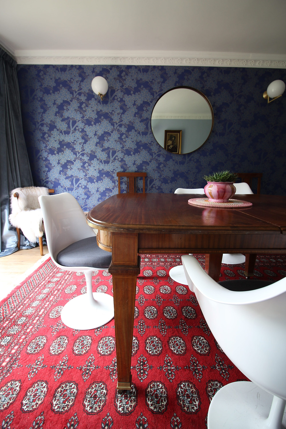 Dining room inspiration with Blue wallpaper Camelia from Little Green and red bukhara rug Tulip chairs and vintage table Flos lights and round mirror