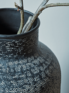 Metal vase close up with branches