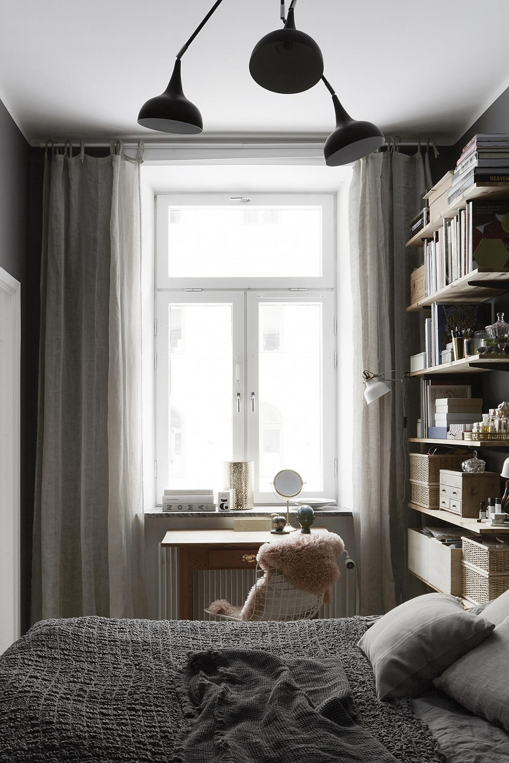 Scandinavian interior design bedroom with black wall and black triple pendant light