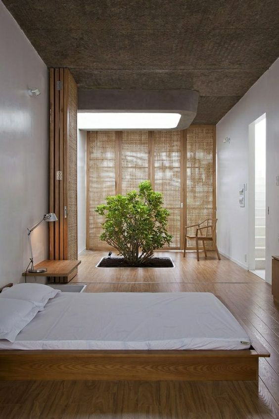 japanese style bedroom with rattan curtains, low bed with white duvet and a tree in the room, wood