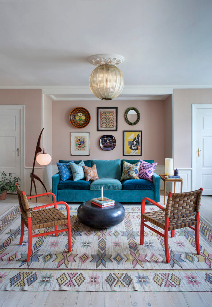 pink wall and blue sofa red chairs and oriental carpet
