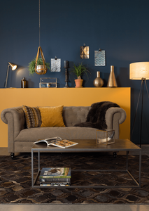 Dutchbone coffee table styling ideas and brass lamps in front of blue painted wall and ethnic rug eclectic styling