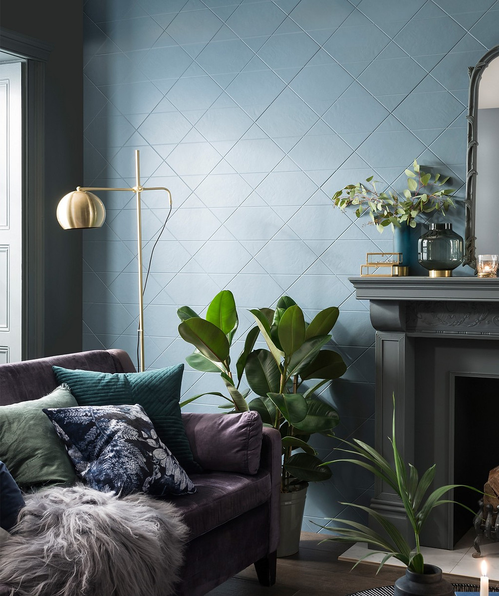 living room with blue wall tiles in diamond pattern grey fireplace surround and brass lamp purple velvet sofa