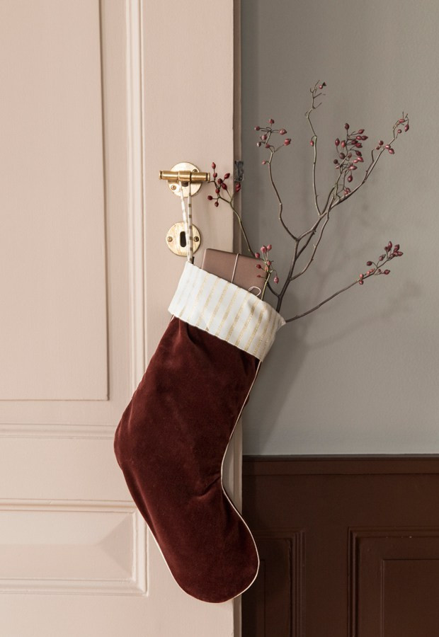 burgundy velvet Christmas stocking hanging from a door with brass handle and pink colour via Ferm Living