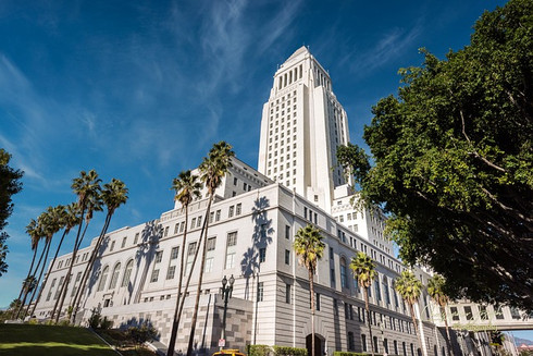 Los Angeles City Hall in the daytime against a bright blue sky.