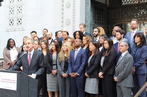 City Attorney Mike Feuer leads an outdoor press conference on the steps of City Hall with about 30 people standing behind him.