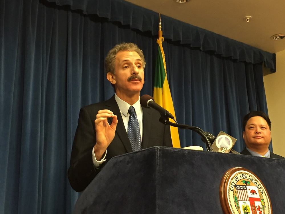 Man in a dark suit with a white shirt and blue tie at a blue podium which has the City of Los Angeles official seal affixed to the front of it, speaking into a microphone. Another man is to his right.