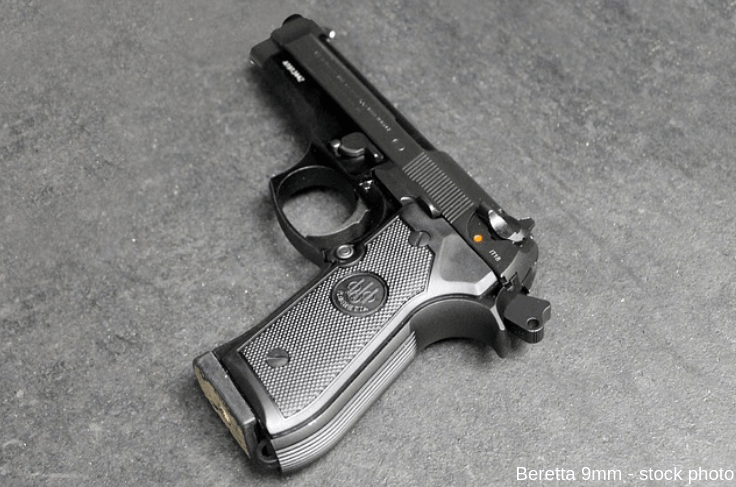 Stock photo of a metal Beretta 9-millimeter pistol on concrete.