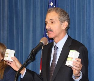Man at podium holding boxes of vitamins