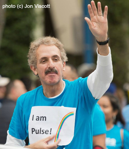 "File photo of City Attorney Mike Feuer in a light blue t-shirt holding a piece of paper that says, ""I Am Pulse!"" taken at a previous LA Pride LGBTQ Parade."