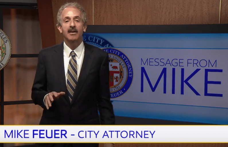 "City Attorney Mike Feuer in a dark brown suit with a brown striped tie in front of a television monitor with the words ""Message From Mike"" on it. Link opens to video."