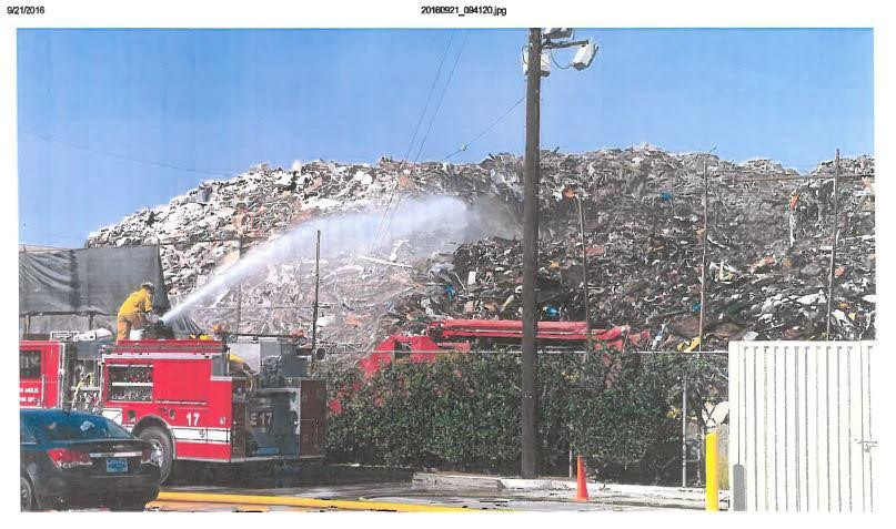 Evidentary photo of a large pile of what appears to be garbage with a red Los Angeles fire truck in front of it and a fire fighter shooting a large plume of water on it.