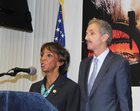 Woman and man at podium speaking into microphone.