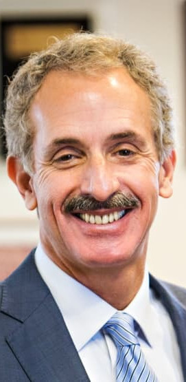 Mike Feuer Official Headshot in which he's smiling, wearing a dark suit and light blue tie with a blurry background.