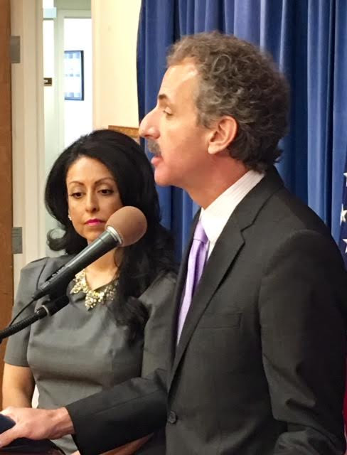 Profile of man in suit with a purple tie speaking into a microphone, a woman in a grey dress with long back hair is to his right.