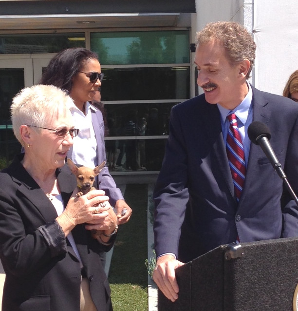 City Attorney Mike Feuer at a podium with a microphone smiling and looking at a tiny puppy being held by Brenda Barnette, the General Manager of the Loa Angeles Animal Services Department.