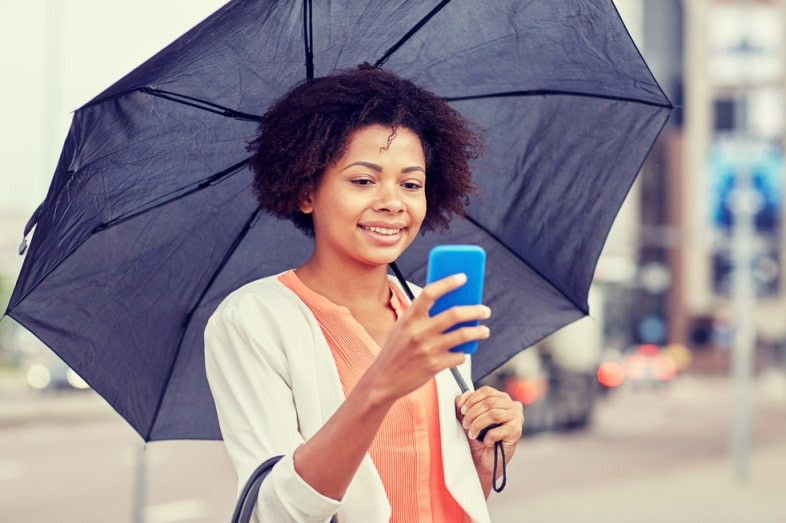 Woman smiling, standing underneath her umbrella and looking at her phone.