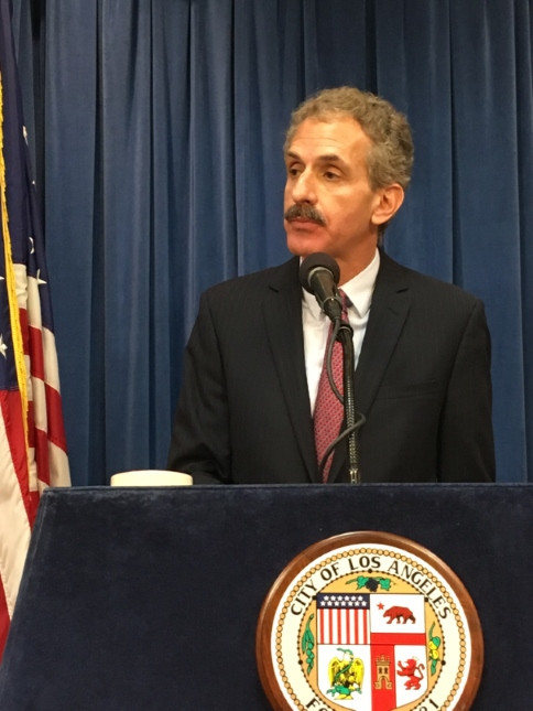 File photo of City Attorney Mike Feuer in a dark suit speaking into a microphone at a podium with the Official City Seal affixed to it.