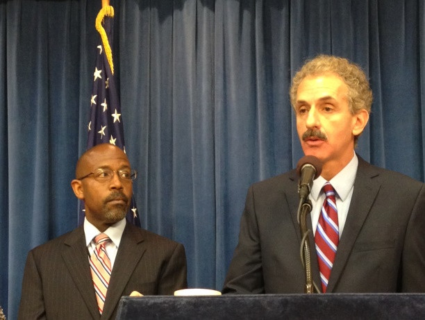 City Attorney Mike Feuer speaking into a microphone next to John Reamer, John Reamer, Inspector of Public Works and head of the Bureau of Contract Administration both standing in front of a blue curtain and the American flag on the left.