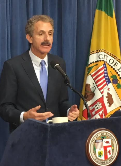 Man in a dark suit and light blue tie and white shirt speaks into a microphone at a podium with the Los Angeles City seal affixed to it, in front of a blue curtain and the California State flag.