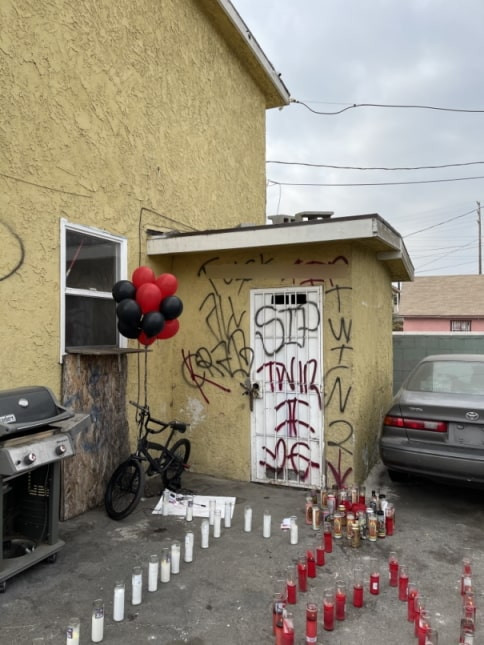Back door area of a yellow apartment complex with graffiti scrawled on it and memorial candles in front of it.