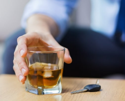 Stock photo of a man reaching for an alcoholic drink on a table next to car keys.