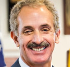 Close up of smiling man with a mustache with the top of his gray suit and white shirt visible. The official photo of Los Angeles City Attorney Mike Feuer.