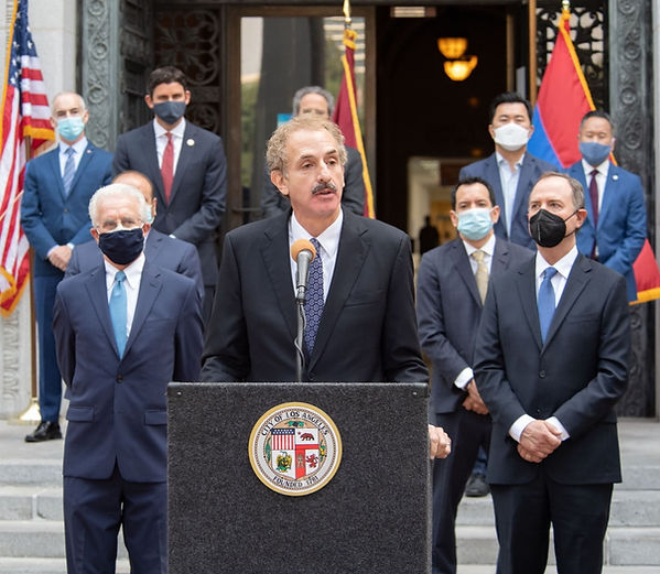 Los Angeles City Attorney Mike Feuer at an outdoor press conference, speaking at a podium, with 8 other men standing behind him, all in suits and ties and masks.