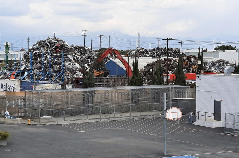 An imposing large mountain of scrap metal towers over a brick wall separating it from a school's basketball court.
