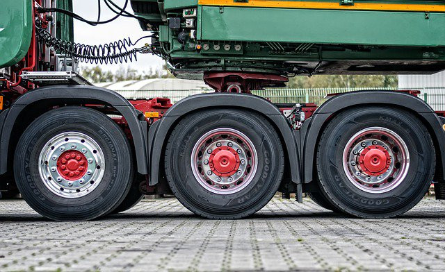 Stock photo close-up of three large tires of a green and yellow 18 wheeler truck.
