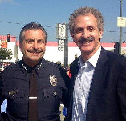 Los Angeles Police Department Chief Charlie Beck in his police uniform next to Los Angeles City Attorney MIke Feuer at an outdoor event.