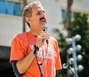 Los Angeles City Attorney Mike Feuer in an orange t-shirt speaking outdoors at a podium holding a hand held microphone.
