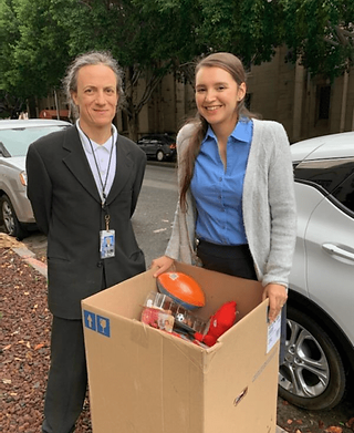 Man in a black suit and white shirt next to a woman with a blue shirt and gray sweater, outside and smiling, standing in front of a cardboard box filled with a nerf football and other toys.
