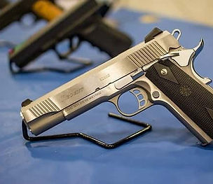 Row of silver and black guns on a table with a blue tablecloth.