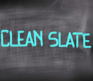 """A graphic image of an old fashioned blackboard with the words """"CLEAN SLATE"""" in teal written on it."""